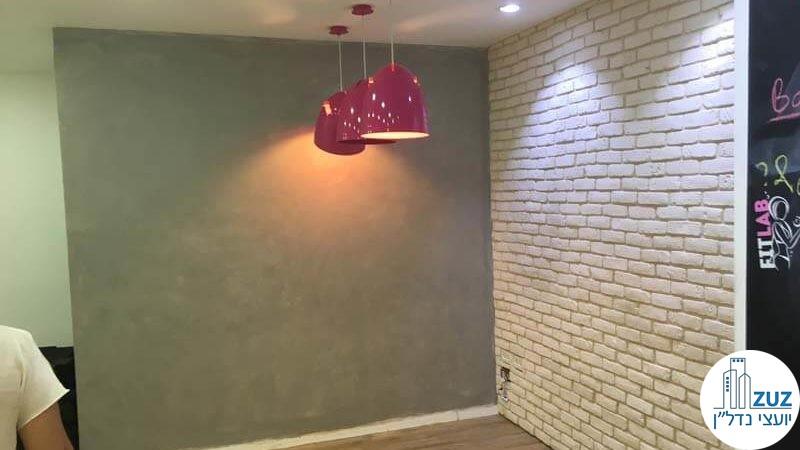 קיר מעוצב עם מנורות ורודות בסטודיו בבניין משרדים בשכונת מונטיפיורי תל אביב